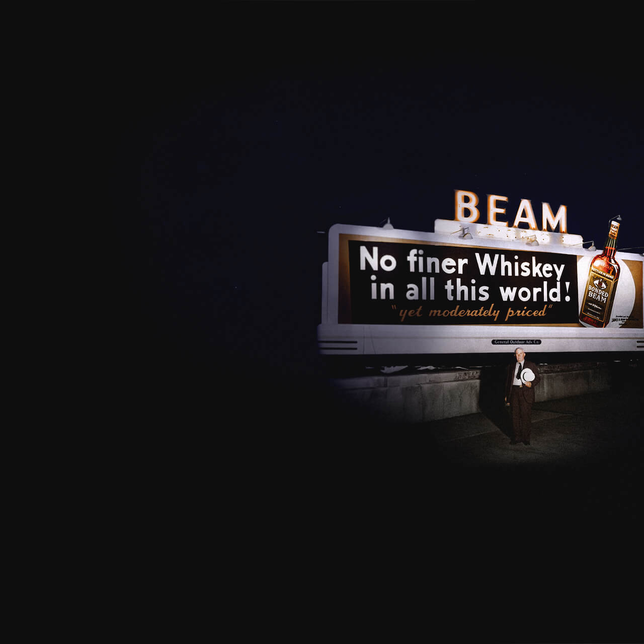 James B. Beam standing in front of a billboard.