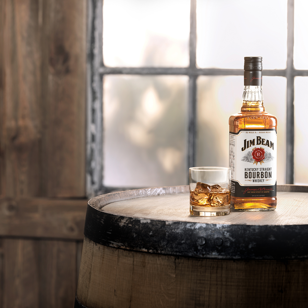 A Bottle of Jim Beam® placed in front of Barrels