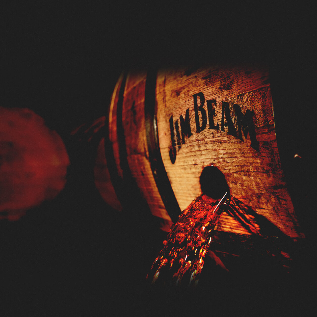 Jim Beam® Whiskey pouring from a Barrel.