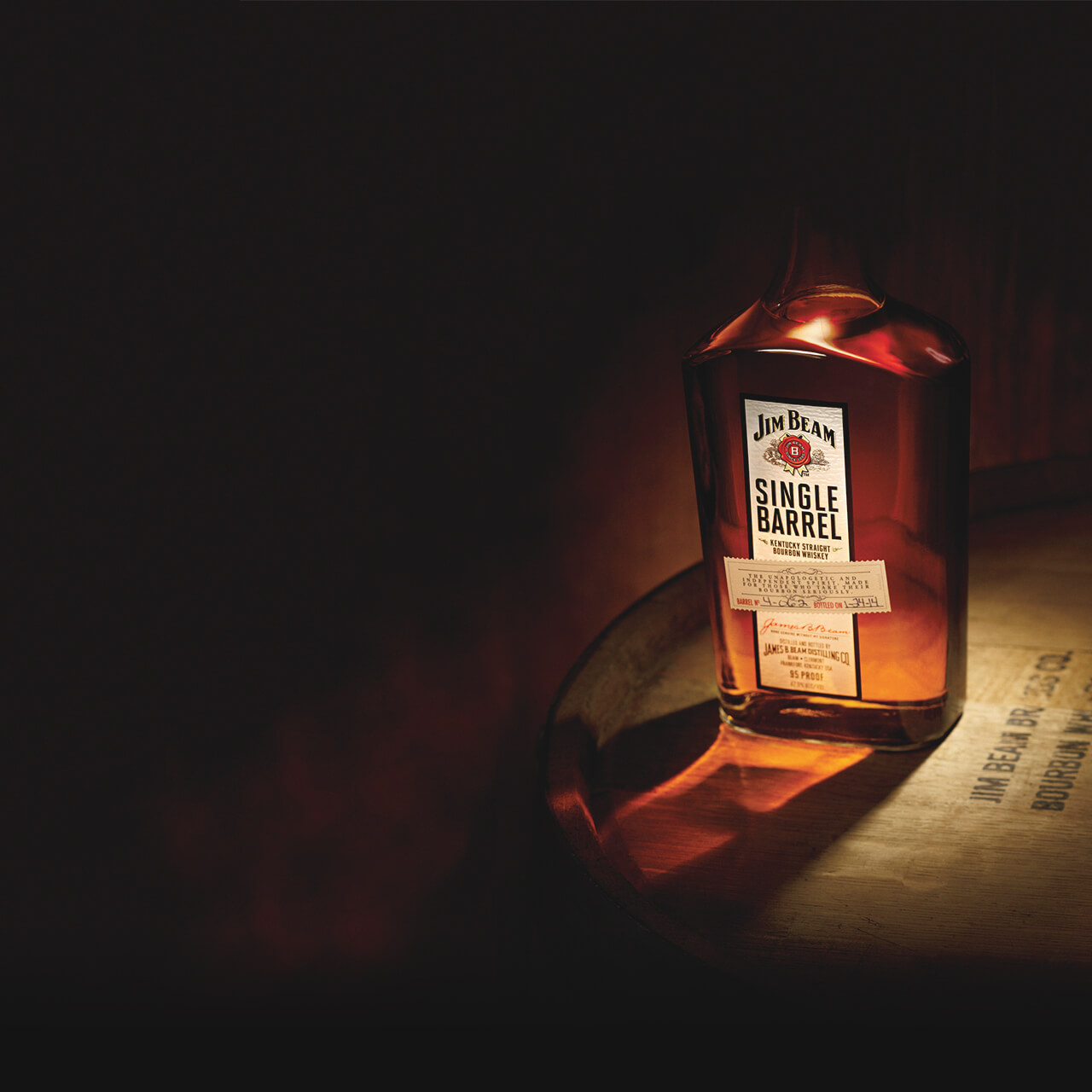 A bottle Jim Beam Single Barrel standing on a barrel.